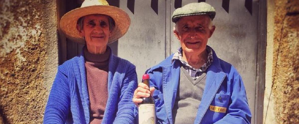 Fotografía de una mujer y un hombre de avanzada edad con una de las botellas de maquina y tabla